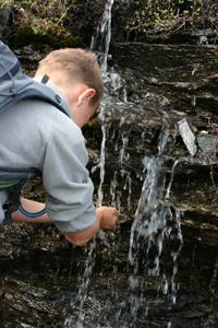 Oscar dricker från ett litet vattenfall